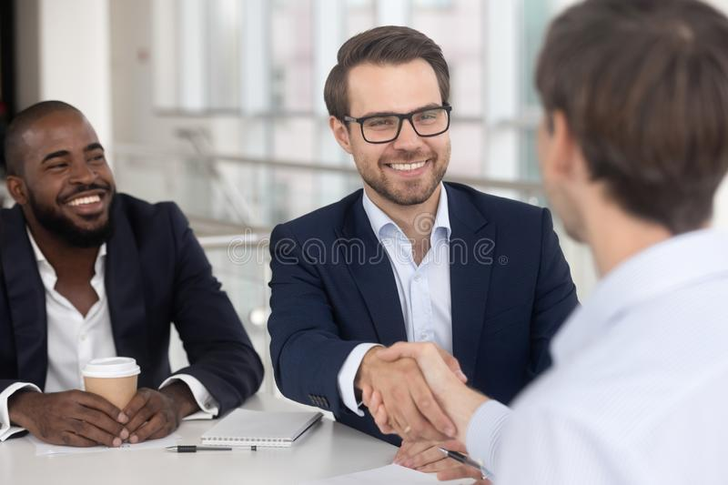Positive diverse business partners shaking hands starting meeting. Cheerful successful businessmen meet at boardroom multiracial entrepreneurs starting stock photography