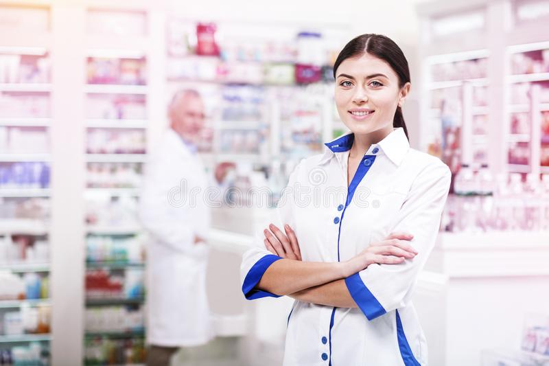 Positive druggist with crossed hands waiting for customers stock image