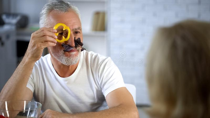 Positive elderly husband playing fresh vegetables, cooking together, joking wife stock image