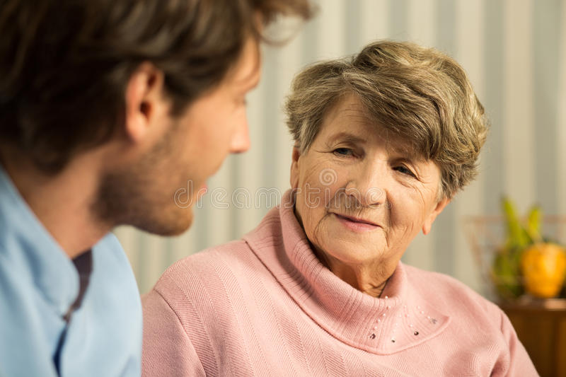 Positive elderly woman with carer. Photo of positive elderly women with young male carer royalty free stock images
