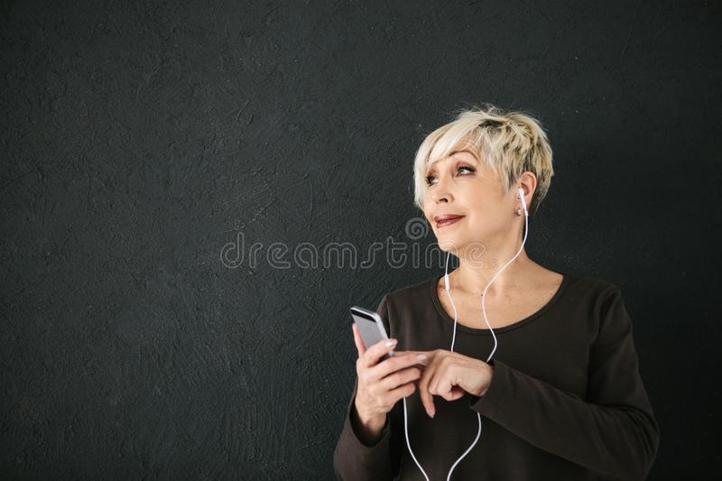 Positive elderly woman listening to music. On a dark background. The older generation and new technologies. Positive elderly woman listening to music. On a dark royalty free stock photos