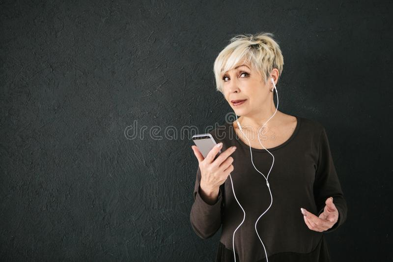 Positive elderly woman listening to music. On a dark background. The older generation and new technologies. stock photography