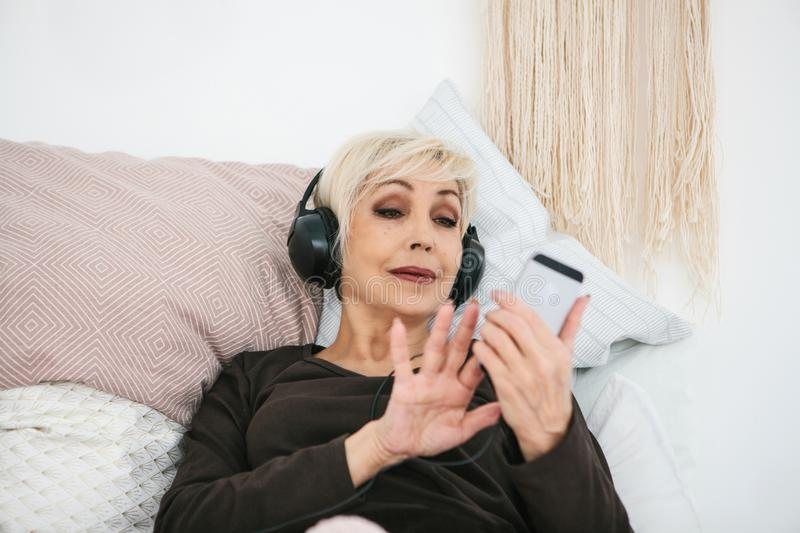 Positive elderly woman listening to music. The older generation and new technologies. stock image