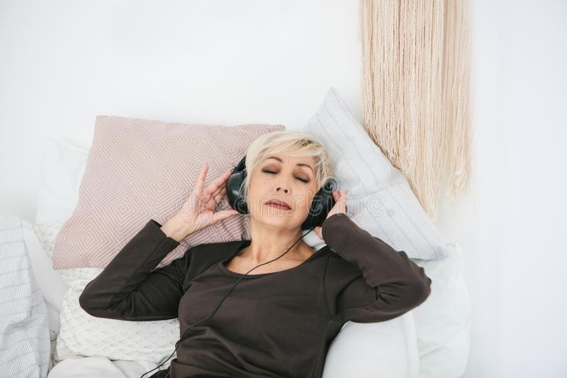 Positive elderly woman listening to music. The older generation and new technologies. royalty free stock photo