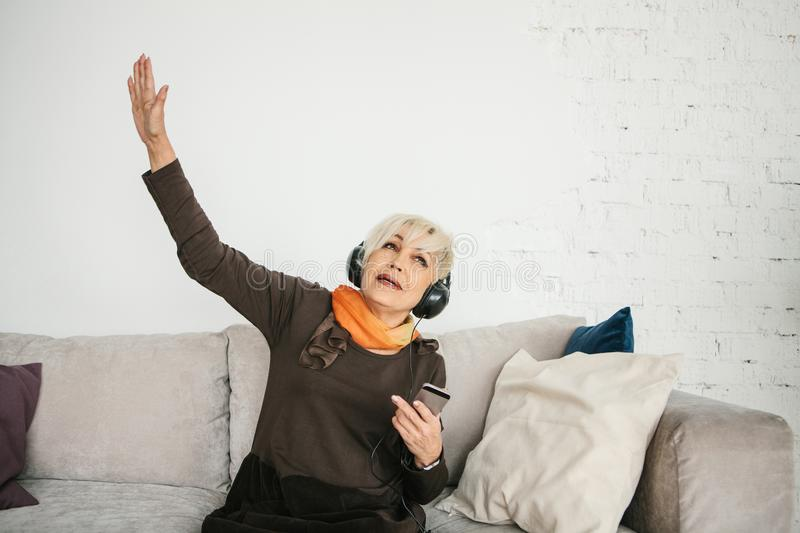 A positive elderly woman listens to music and sings. The older generation and new technologies. stock image