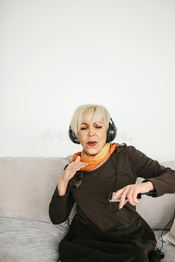 A positive elderly woman listens to music and sings. The older generation and new technologies. A positive elderly woman listens to music and sings. The older stock photography