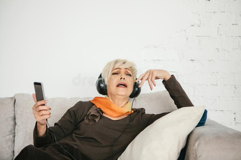 A positive elderly woman listens to music and sings. The older generation and new technologies. A positive elderly woman listens to music and sings. The older stock images