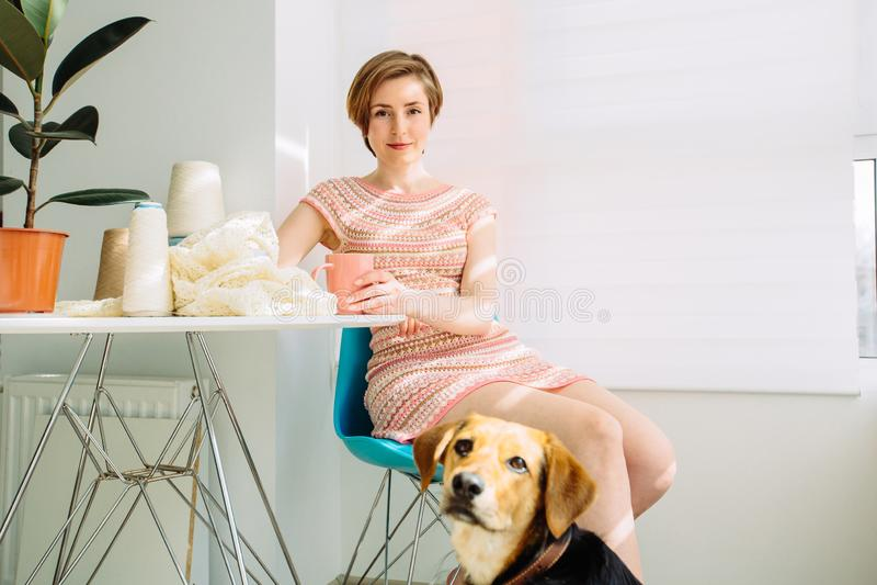 Positive entspannte Frau, die Bruch mit Kaffeetasse an dem gemütlichen Arbeitsplatz zu Hause Innen hat Glückliche Frau mit ihrem  stockfotos