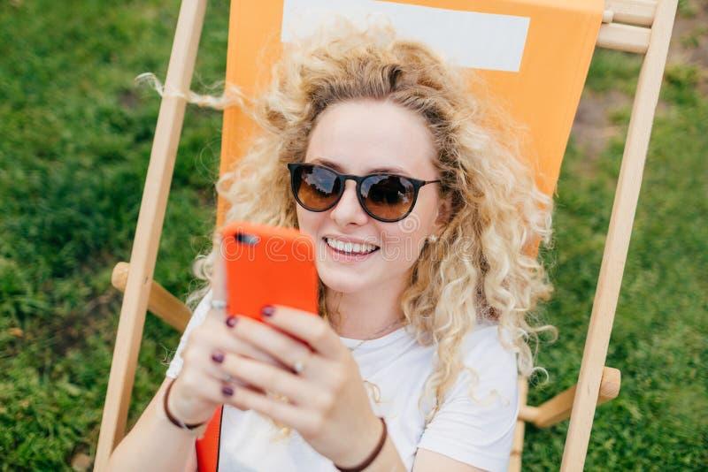 Positive europäische Frau mit freundlichem Lächeln, modernes elektrisches des Gebrauches stockbild