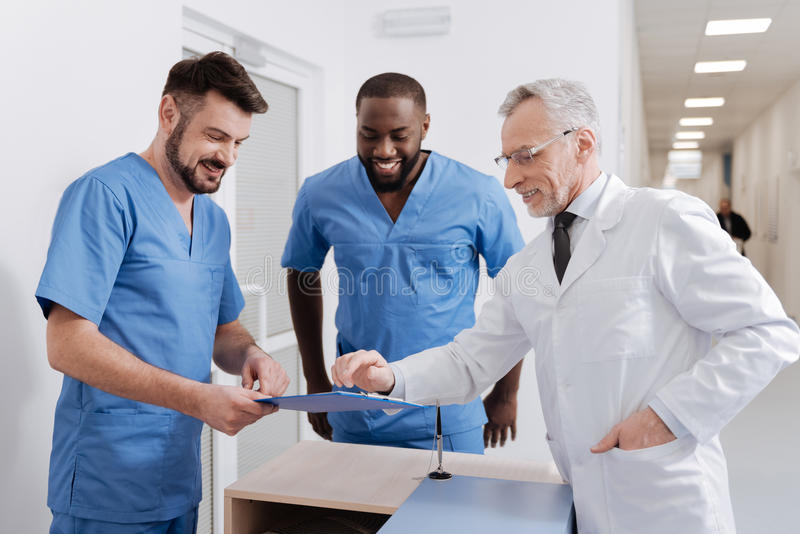 Positive experienced medic checking the quality of work in the hospital. Enjoying discussion with colleagues . Smiling professional old medic working in the royalty free stock photos