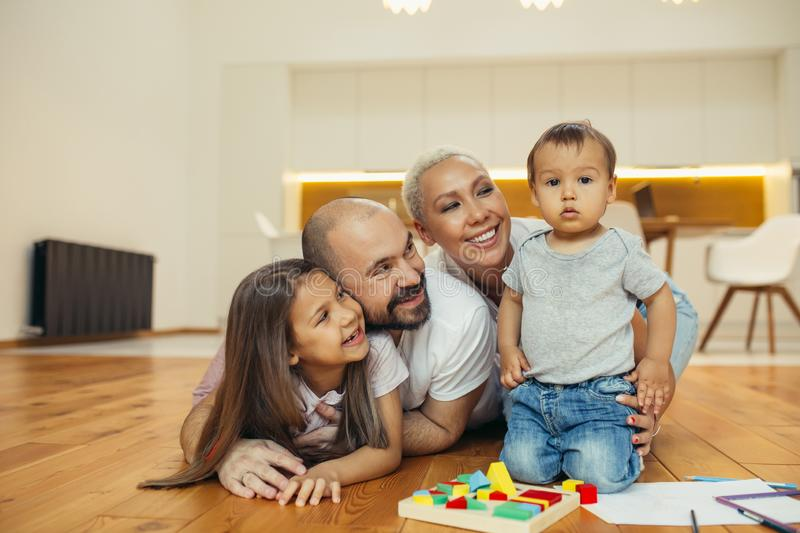 Happy family lying on floor in new countryhouse royalty free stock image