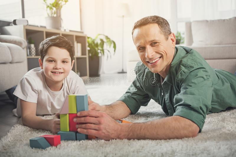Positive father and son enjoying time together at home stock photo