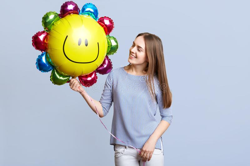 Positive female celebrates her birthday, holds balloon in form of sun, has festive mood, dressed in elegant clothing, waits for gu stock photos
