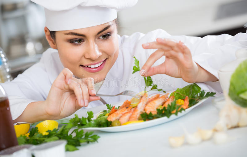 Positive female cook with shrimps, herbs and lemon stock images