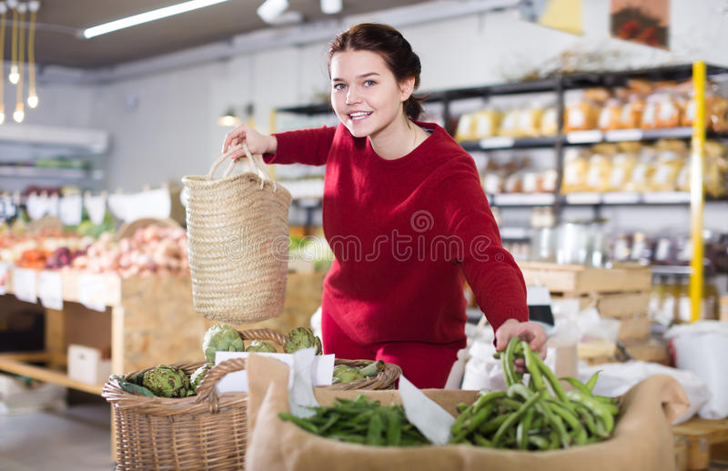 Positive female customer looking green beans stock image