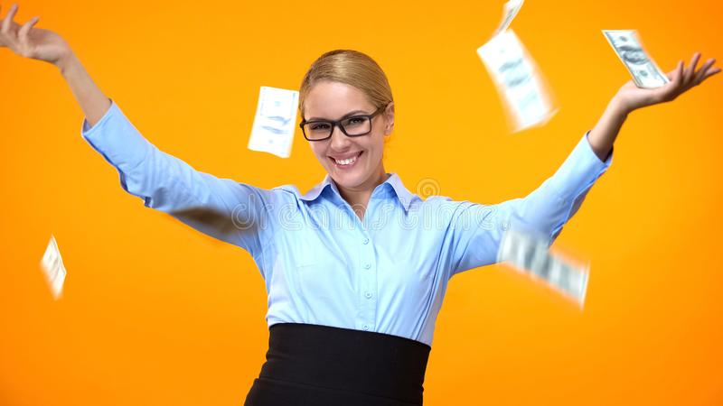Positive female in formal suit under falling dollars, financial independence. Stock photo royalty free stock photography