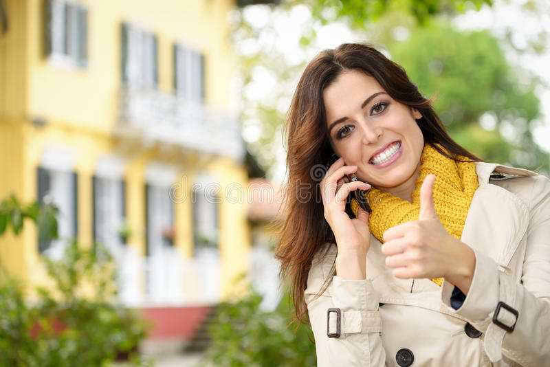 Positive female home owner calling by phone. In her country house garden. Confidence woman approving with thumbs up while talking on cellphone and smiling stock photography