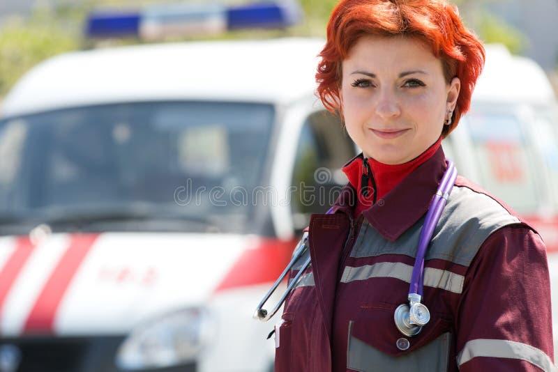 Positive female paramedic. On ambulance vehicle background stock photos
