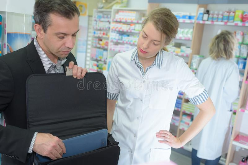 Positive female pharmacist counseling customer stock photo