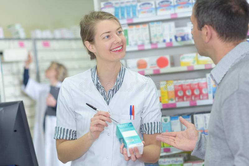 Positive female pharmacist counseling customer royalty free stock photo