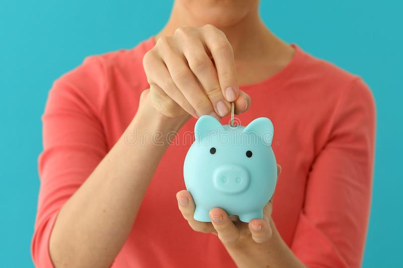 Positive female putting coin in piggybank, planning budget, financial savings royalty free stock image