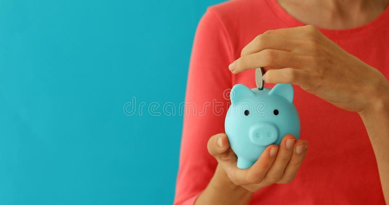 Positive female putting coin in piggybank, planning budget, financial savings stock image