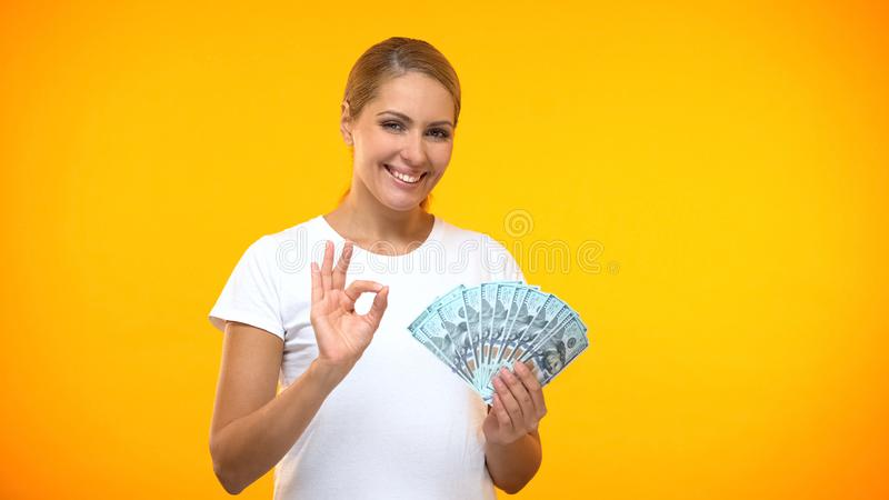 Positive female showing ok gesture holding dollars in hand, financial investment royalty free stock photos