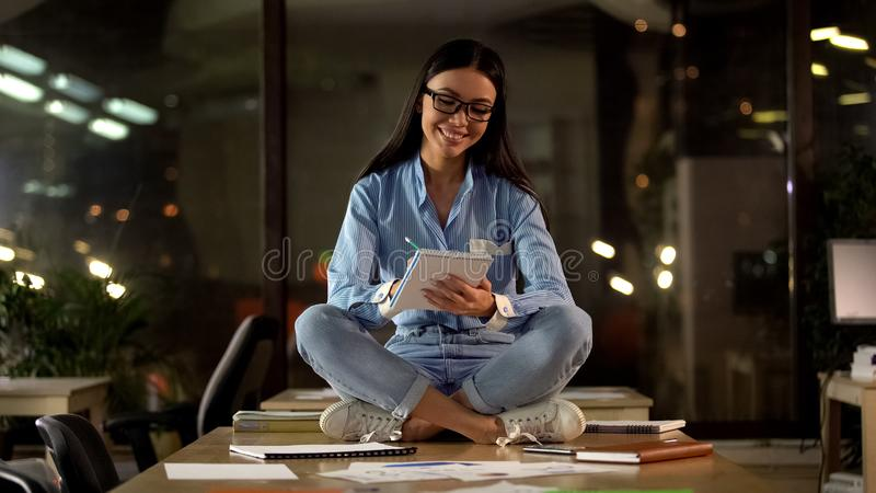 Positive female sitting lotus pose writing in notebook, modern work environment royalty free stock images
