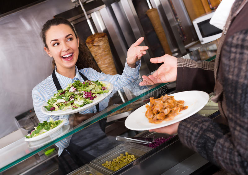 Positive female worker serving customer stock photo