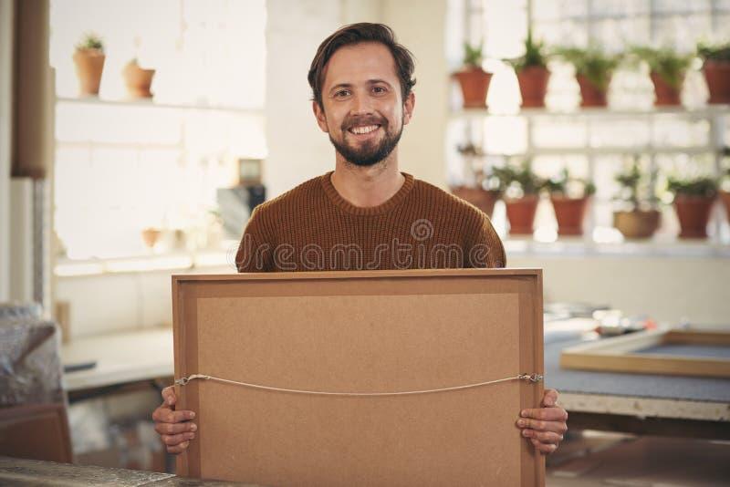 Positive framer smiling his workshop holding a framed item stock photos