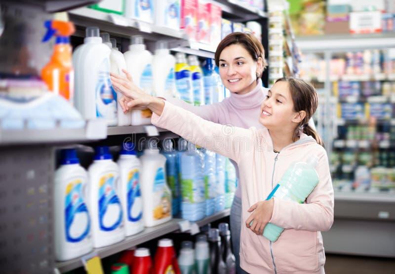 Positive Frau mit der Tochter, die Reiniger wählt stockfotos