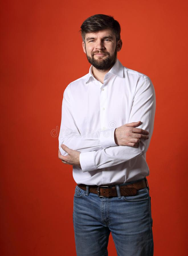 Positive friendly bearded businessman posing with folded arms in. Fashion white style shirt looking happy on bright orange background. Closeup portrait stock image