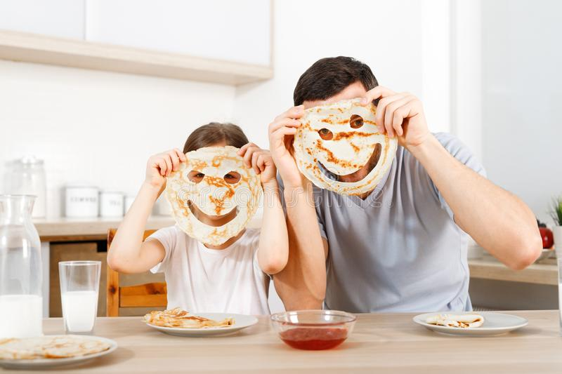 Positive friendly daughter and father make funny faces from pancakes, looks through handmade eyes, sit at kitchen, have stock image