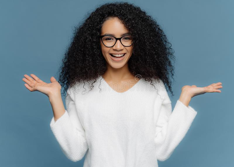 Positive friendly young woman with Afro appearance, spreads palms, holds invisible object, has charming smile, healthy skin, wears royalty free stock photos
