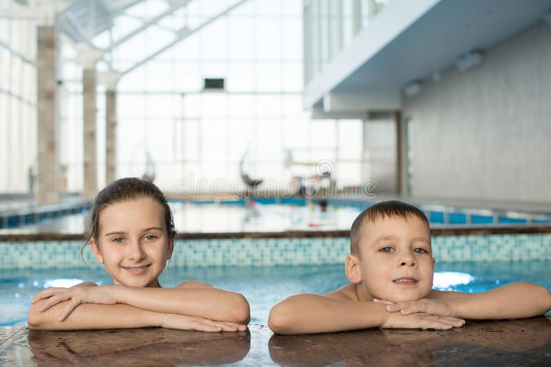 Positive friends leaning on swimming pool edge stock photography
