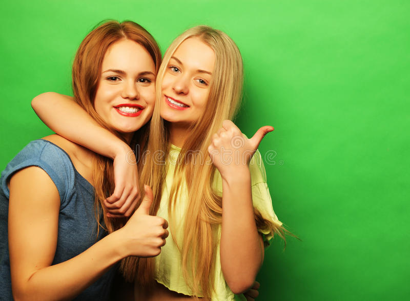 Positive friends portrait of two happy girls - funny faces, emo stock photo