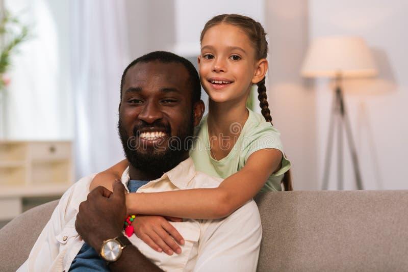 Positive frohe geumgürtete Stellung hinter ihrem Vater stockbilder