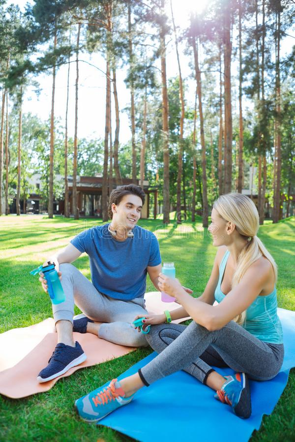 Positive frohe Leute, die auf Yogamatten sitzen lizenzfreies stockbild