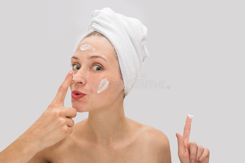 Positive and funny picture of young woman looks on camera and touches her nose with finger. She has some face cream on royalty free stock photos
