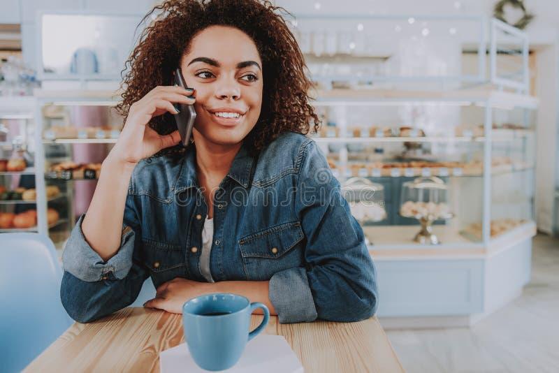 Positive gelockte junge Frau, die am Telefon spricht lizenzfreie stockfotos