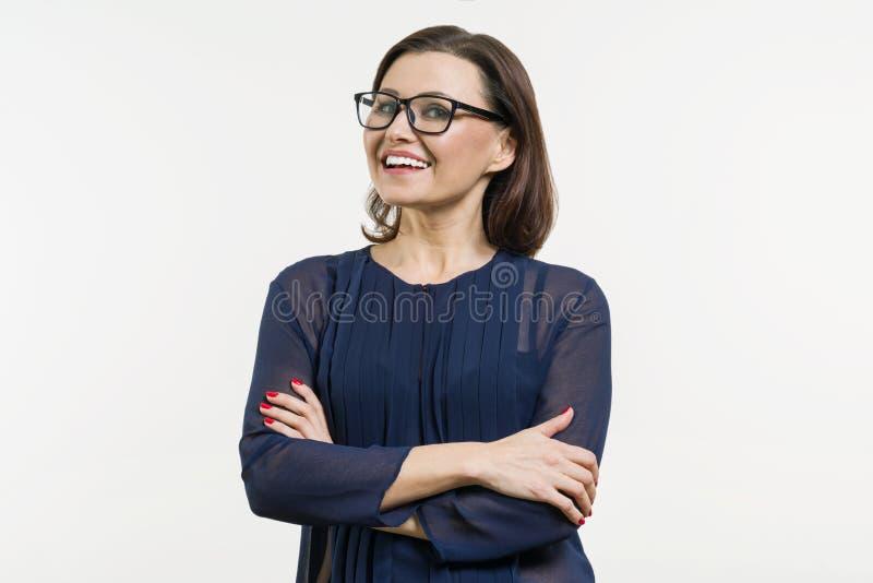 Positive Geschäftsfrau des Mittelalters aufwerfend über Weiß mit den Armen gekreuzt lizenzfreie stockfotos