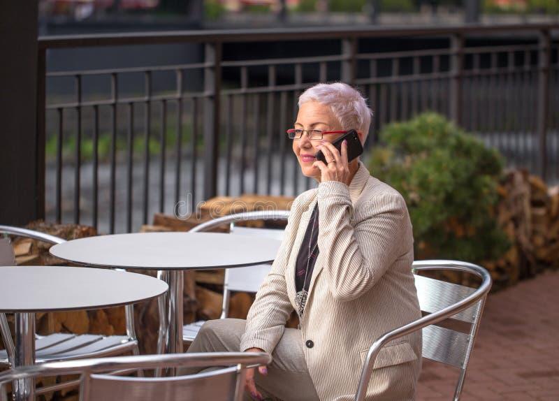 Positive Geschäftsfrau, die am Telefon in einem Straßencafé spricht stockbilder