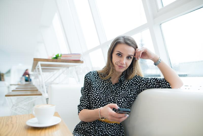 Positive Geschäftsfrau mit einem Telefon in ihren Händen, die am Fenster auf der Couch in einem stilvollen modernen Café sitzen stockbild
