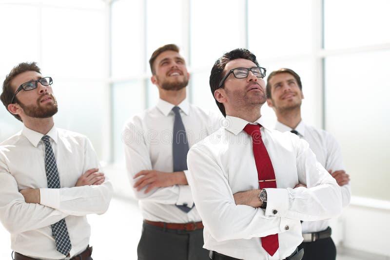 Positive Geschäftsgruppe, die oben mit dem Träumen des Ausdrucks schaut stockbilder