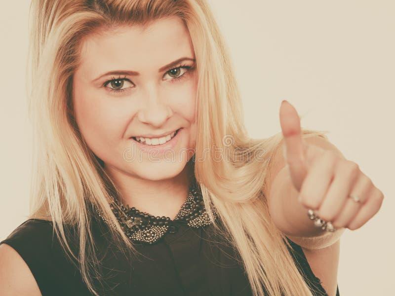 Smiling blonde woman making thumb up gesture stock image