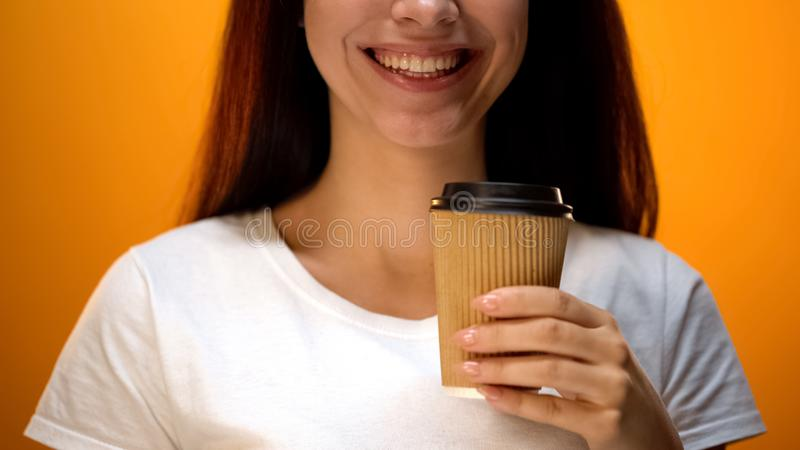 Positive girl holding coffee paper cup and smiling  on orange background stock images