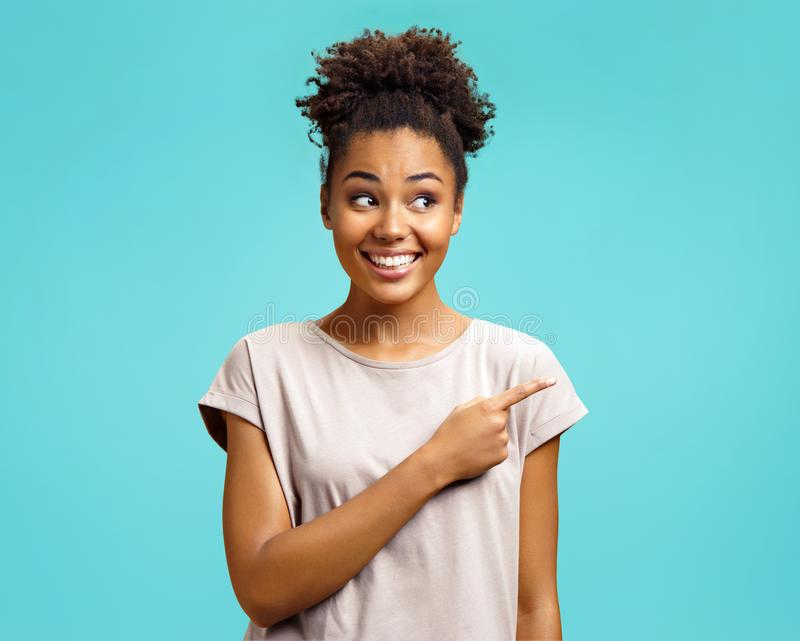 Positive girl indicates with forefinger, shows place for your advertisement. stock images