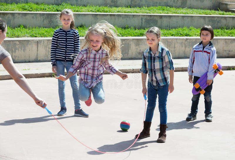 Positive girl jumping while jump rope game. With friends outdoor royalty free stock photo
