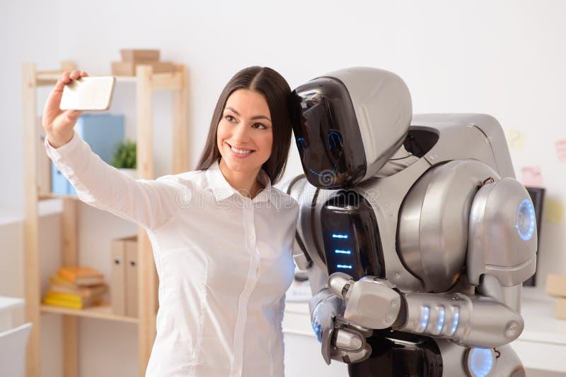 Positive girl making selfies with robot stock image