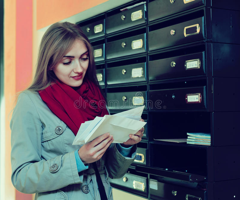 Positive girl in outwear receiving correspondence. At hall entrance stock image
